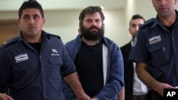 FILE - Israeli Yosef Haim Ben David (C), convicted in the killing of 16-year-old Palestinian Abu Khdeir, arrives at a court in Jerusalem, April 19, 2016. Ben David was sentenced Tuesday to life plus 20 years in prison.