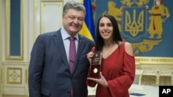 Ukraine's President Petro Poroshenko and Eurovision winner Jamala pose for a photograph after Poroshenko awarded the winner with a state award, in the Presidential Office in Kyiv, Ukraine, May 16, 2016.
