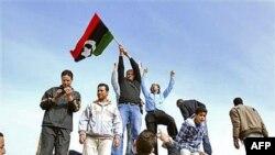 Bingazi'deki bir polis karargahında eski Libya bayrağı tutan bir göstericiler