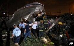 Nhân viên cứu hộ tại hiện trường vụ tai nạn xe lửa trậy đường ray ở Philadelphia.