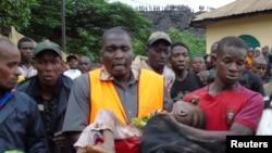 Abajejwe gutabara bafise umwana yarokotse igihe umwavu wasenyukira ku mazu mu micungararo ya Conakry, Gineya.