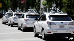 FILE - Google self-driving Lexus cars are seen at a Google event outside the Computer History Museum in Mountain View, California, May 13, 2014.