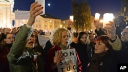 FILE - People hold candles aloft as they protest against judicial reforms proposed by the president and ruling party Law and Justice, in Warsaw, Poland, Oct. 1, 2017.