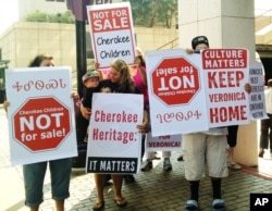 File photo shows Cherokee tribe members protesting the adoption of a 3-year-old Cherokee girl by a non-Native couple, Wednesday, Aug. 14, 2013 in Tulsa, OK.