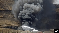 Firefighters battle a huge fire after several explosions were set off at the army's First Armored Division headquarters in Sanaa, Yemen, Oct. 18. 2012.
