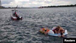 A Canadian Coast Guard ship tows floatation devices used by Americans to the Canadian side of the St. Clair River between Michigan and Ontario, Aug. 21, 2016.