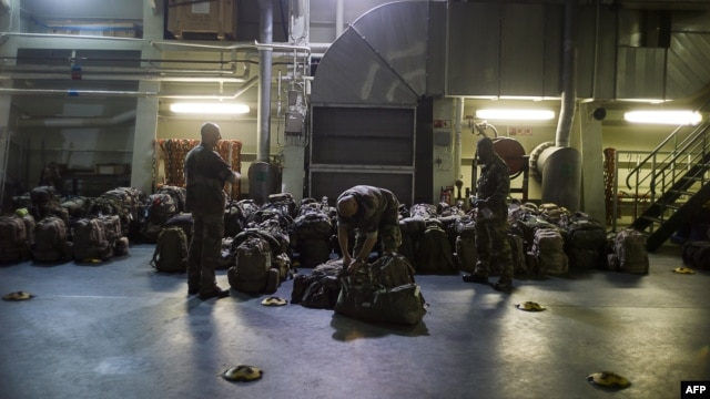 FILE - French military packing their bag aboard the French Navy amphibious assault ship BPC Dixmude moored, in the port of Douala.