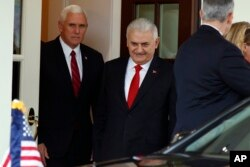 FILE - Vice President Mike Pence escorts Turkish Prime Minister Binali Yildirim to his car after a meeting at the White House in Washington, Nov. 9, 2017.
