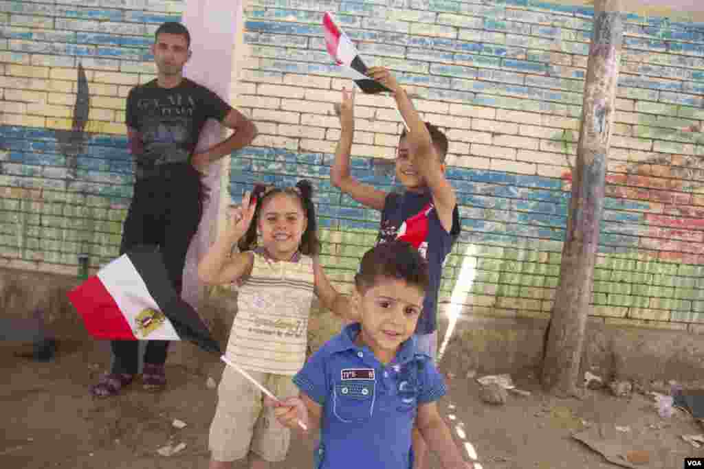Children wave flags outside a polling station in Cairo, May 27, 2014. (Hamada Elrasam /VOA)