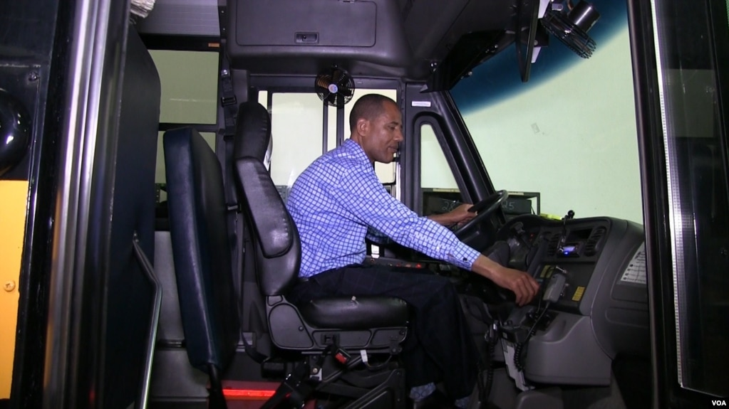 Tashitaa Tufaa drives one of his company's largest school buses, which seats 70 pupils, in Fridley, Minnesota, Aug. 9, 2017. Tufaa's company owns nearly 300 buses. (Photo: Abdi Mohamud for VOA)