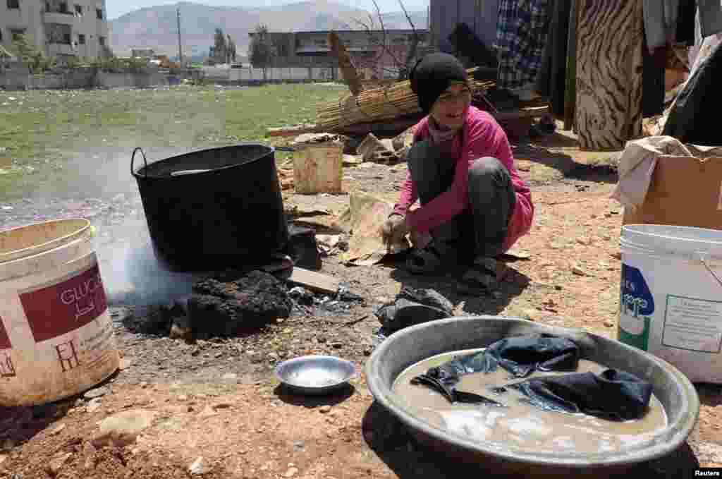 A young Syrian girl keeps her fire lit with cardboard at a refugee camp in the eastern Lebanese town of Anjar near the Syrian border, May 13, 2014.