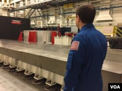 Astronaut Rex Walheim looking at the 'barrel' at Ingersoll Machine Tools in Rockford, Illinois. (K. Farabaugh/VOA)