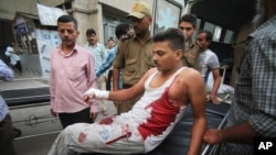 An injured Indian civilian of cross border firing gets down from an ambulance at the Government Medical College hospital in Jammu, India, Friday, Aug. 28, 2015.