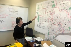In this Nov. 22, 2019, photo, Detroit 2020 Census Campaign executive director Victoria Kovari looks over a Detroit map showing city neighborhoods that were under-counted in the 2010 census. (AP Photo/Corey Williams)