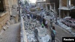 Người dân xem xét thiệt hại tại một địa điểm bị trúng pháo kích của phiến quân tại khu vực do chính phủ Syria kiểm soát ở Aleppo, Syria, ngày 11 tháng 7 năm 2016.