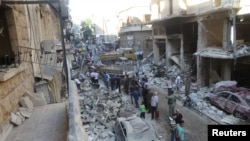 People inspect the damage at a site after it was hit by shelling carried out by rebels at Syrian government-held areas of Aleppo, Syria, in this handout picture provided by SANA on July 11, 2016.