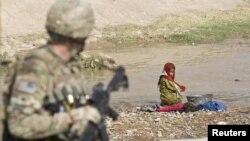 Un soldado estadounidense monta guardia mientras una niña lava ropa en Senjaray, en el sur de Afganistán.