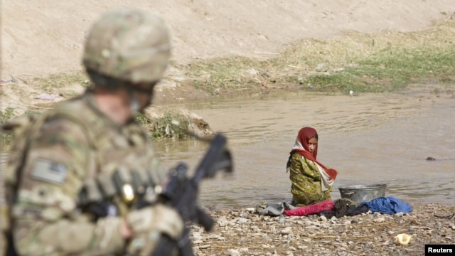 An Afghan girl washing clothes in a river looks at a US Army soldier in the town of Senjaray, southern Afghanistan May 29, 2012.