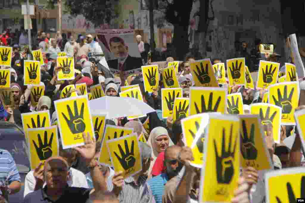 Demonstrators hold up four fingers, a symbol of their solidarity with the the destroyed sit-in protest known as Rabaa, which means four or fourth in Arabic, Cairo, August 23, 2013. (H. Elrasam for VOA)