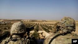 Soldados estadounidenses observan hacia la frontera con Turquía, en Manbij, al norte de Siria.