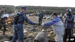 Mwanajeshi wa Marekani akisaidia katika kazi za kusafisha taka baada ya janga la tsunami katika mji wa pwani wa Misawa , Japan.