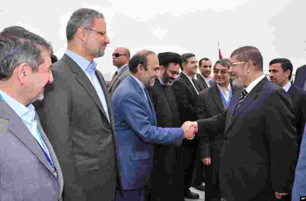 Iran's President Mahmoud Ahmadinejad looks on as Egyptian President Mohamed Morsi shakes hands with the Iranian delegation at the airport in Cairo, Egypt, February 5, 2013. (Egyptian Presidency Handout)