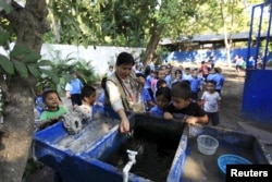 Health promoter Marielos Sosa deposits fishes in a water tank at a local school for a mosquito control project at San Diego village in La Libertad, El Salvador, Feb. 1, 2016.