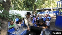 Health promoter Marielos Sosa deposits fishes in a water tank at a local school for a mosquito control project at San Diego village in La Libertad, El Salvador, Feb. 1, 2016. Sosa and a group of young volunteers developed a project which they say uses Sambo fish in water tanks and deposits to prevent the breeding of mosquitoes that transmit zika, dengue and chikungunya.