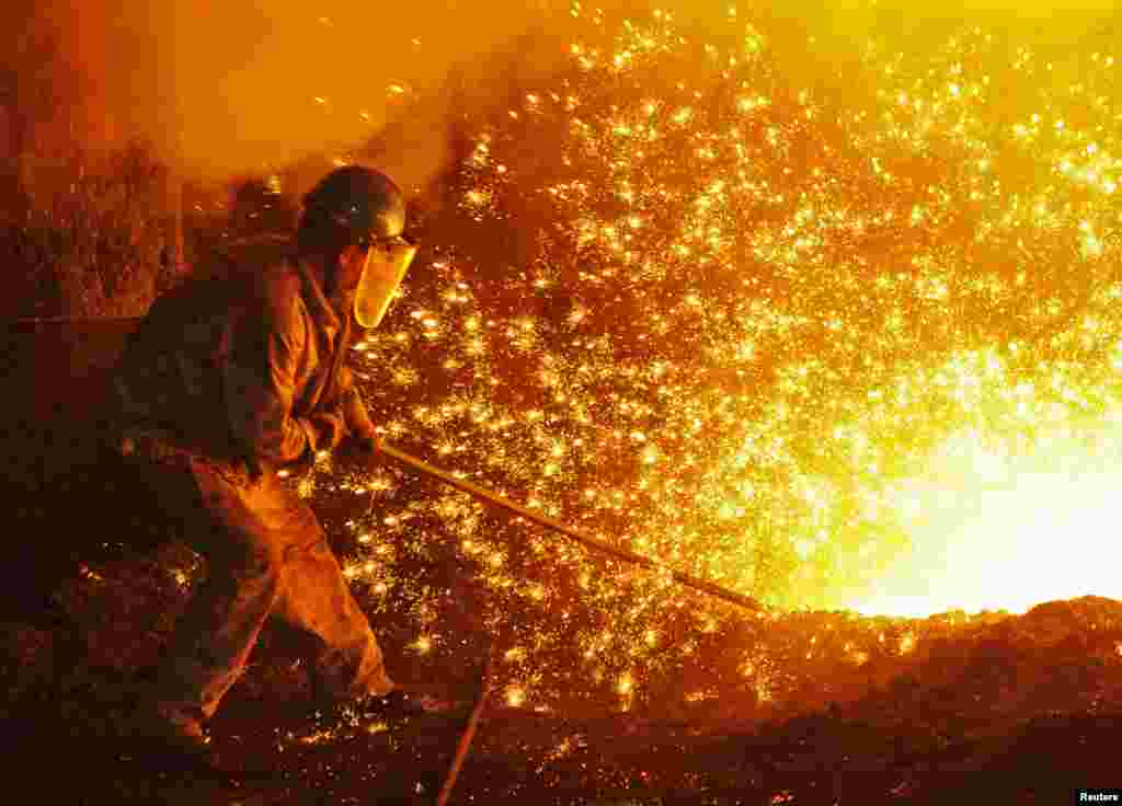 An employee works next to molten iron at a steel mill of Dongbei Special Steel in Dalian, Liaoning province, China.