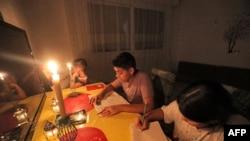 Anak-anak belajar di malam hari, diterangi lilin akibat pemadaman listrik di sebuah hunian di ibu kota Libya, Tripoli, 26 Agustus 2021.