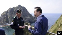South Korean President Lee Myung-bak, right, talks with police officer Yoon Jang-soo as Lee visits islands called Dokdo in Korea and Takeshima in Japan, August 10, 2012.