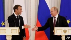 Russian President Vladimir Putin (R) and French President Emmanuel Macron, shake hands after their joint news conference following the talks at the Konstantin palace with the statue of the Peter The Great in the background just outside St. Petersburg, Russia, May 24, 2018.