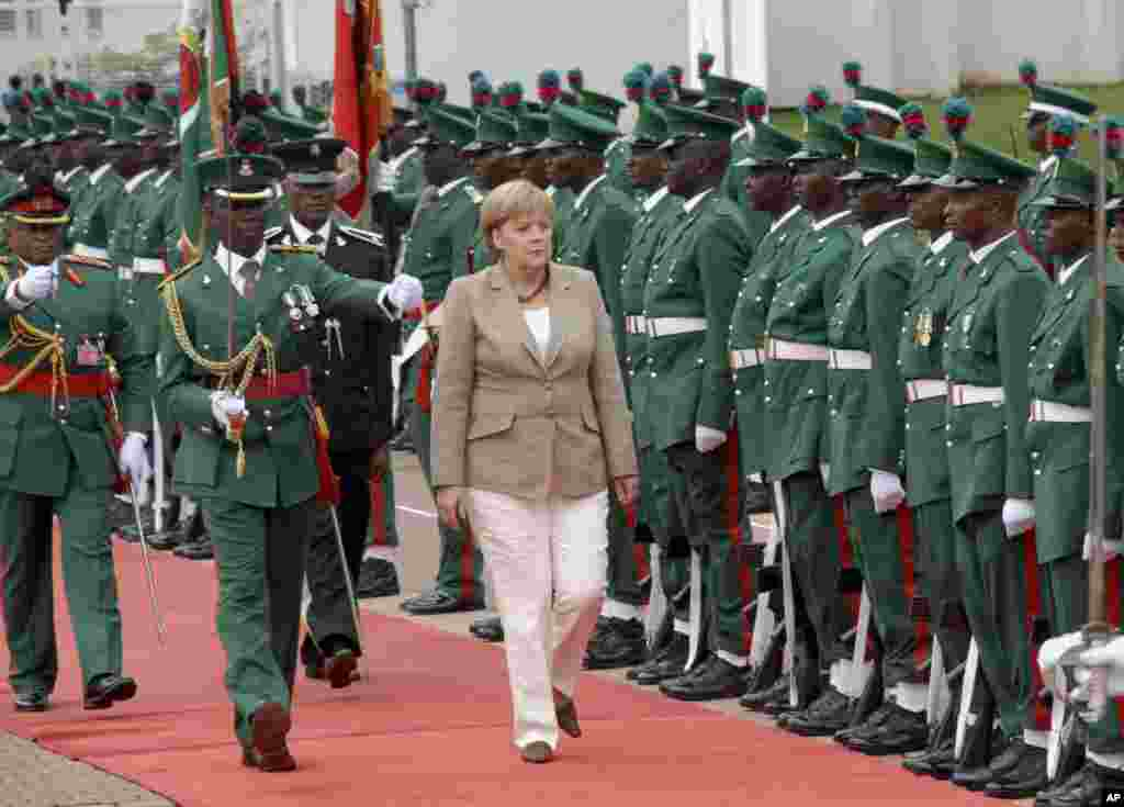 German Chancellor, Angela Merkel, centre, inspects a guard of honor, during her visit to the state house, in Abuja, Nigeria, Thursday, July 14, 2011.