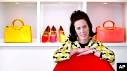 FILE - In this May 13, 2004 file photo, designer Kate Spade poses with handbags and shoes from her next collection in New York.