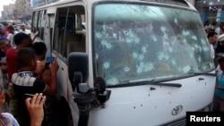 Orang-orang berkerumun di sekitar bis yang diserang laki-laki bersenjata di kota pelabuhan Yaman selatan, Aden, 15 Juni 2014.