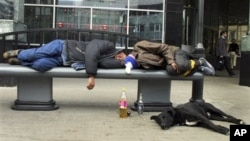 Men sleep on a bench in downtown Moscow after drinking.