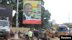 FILE - People pass in front of an electoral campaign poster for incumbent President Alpha Conde in Conakry, Guinea, Sept. 10, 2015.