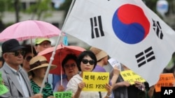 FILE - South Koreans hold signs and a national flag during a rally in support of the deployment of the advanced THAAD missile defense system, in Seoul, South Korea, July 18, 2016.
