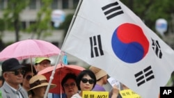 韩国民众手举标语牌和国旗集会支持在韩国部署萨德导弹防御系统(2016年7月18日)