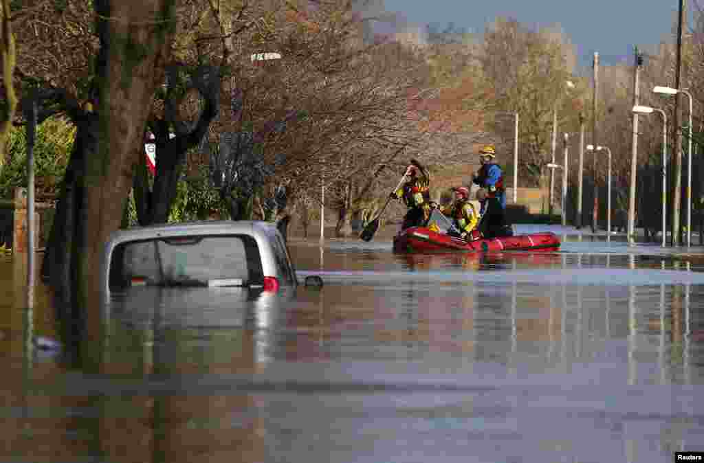 Members of the emergency services rescue local residents by boat from a flooded residential street in Carlisle, Britain.