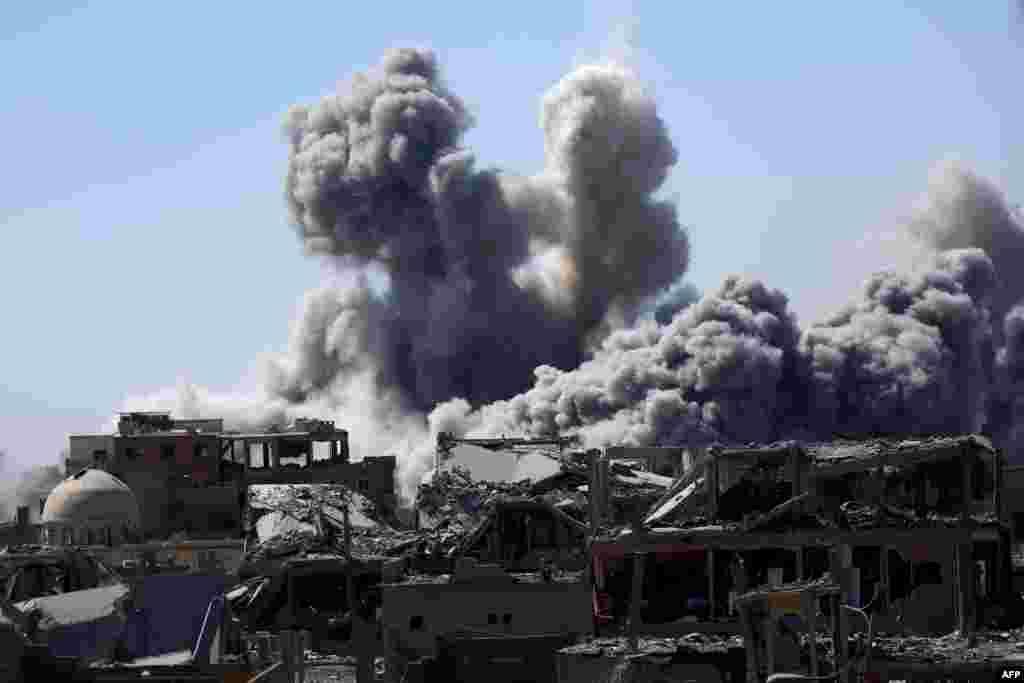 Asap mengepul di kota Raqa, Suriah utara ketika lasykar koalisi Suriah yang didukung Amerika berusaha merebut kota ini dari tangan militan ISIS.