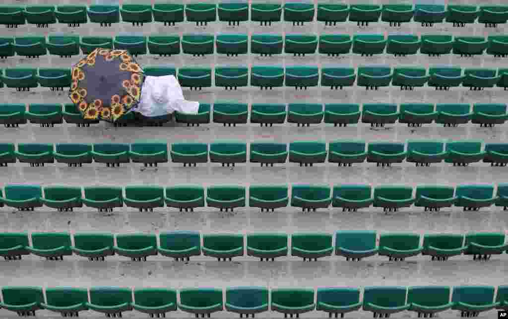 A spectator sits under an umbrella at the Roland Garros stadium as matches for the French Open tennis tournament were delayed because of the rain in Paris.