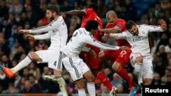 Liverpool and Real Madrid players jump for a ball during their Champions League Group B soccer match in Madrid November 4, 2014.
