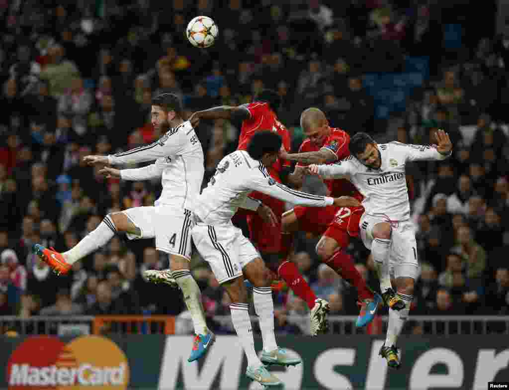 Liverpool and Real Madrid players jump for a ball during their Champions League Group B soccer match in Madrid.