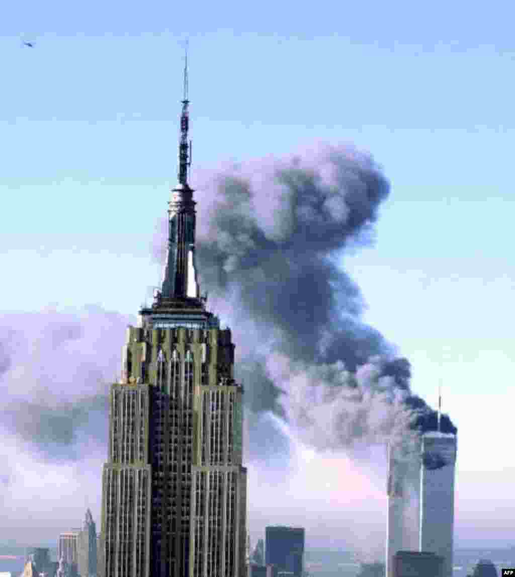 Plumes of smoke pour from the World Trade Center buildings in New York Tuesday, Sept. 11, 2001. Planes crashed into the upper floors of both World Trade Center towers minutes apart Tuesday in a horrific scene of explosions and fires that left gaping holes