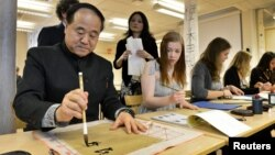 Mo Yan, Chinese winner of the 2012 Nobel Prize in Literature, demonstrates Chinese calligraphy to a student during a visit to a high school in Lidingo, outside Stockholm, Dec. 7, 2012.