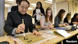 Ông Mạc Ngôn chỉ cho một học sinh cách viết chữ Trung Quốc khi ông đến thăm một trường trung học ở ngoại ô Stockholm 7/12/12