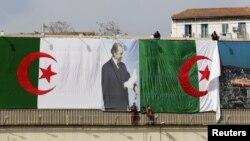Des employés de la ville installe le drapeau algérien et un poster du président Abdelaziz Bouteflika, à Alger, en Algérie, le 26 avril 2016.