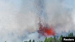 Lava dan asap terlihat setelah letusan gunung berapi di taman nasional Cumbre Vieja di El Paso, Pulau Canary La Palma, 19 September 2021.