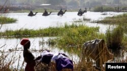 FILE - Nigerians fleeing Boko Haram attacks continue to enter Chad; men on camels cross the water as a woman washes clothes in Lake Chad at Ngouboua, Jan. 19, 2015.